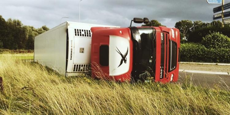 Vrachtwagen op zijn kant op rotonde naar A7