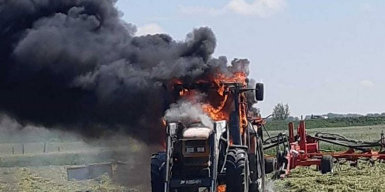 Tractor in brand midden op een weiland in Schagen