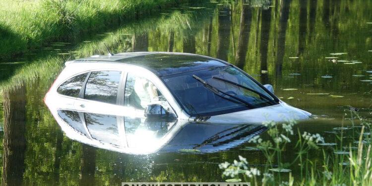Auto belandt in het water naast Dijkgraaf Grootweg in Andijk