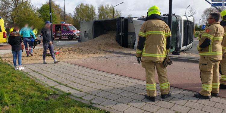 Vrachtwagen met zand kantelt op rotonde